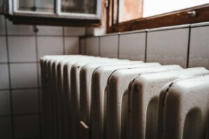 white radiator heater beside brown wooden window
